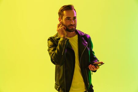 Attractive confident young man wearing leather jacket standing isolated over yellow background, listening to music with wireless earphones while holding mobile phone