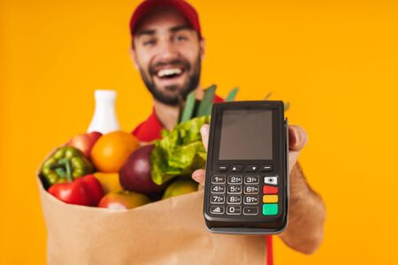 Portrait of optimistic delivery man in red uniform holding payment terminal and paper bag with food products isolated over yellow background Standard-Bild - 129805987