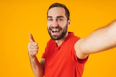 Portrait of delighted man in red t-shirt laughing and showing thumb up while taking selfie photo isolated over yellow background