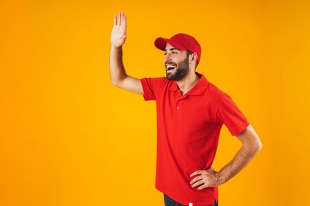 Portrait of happy delivery man in red t-shirt and cap smiling and waving at copyspace isolated over yellow background Standard-Bild - 129805990