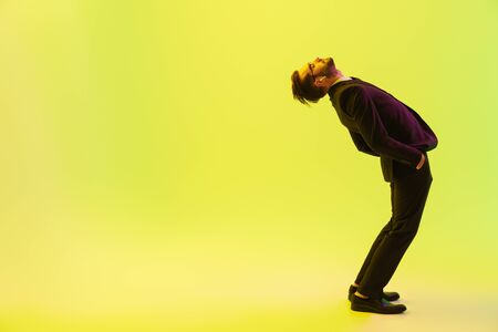 Handsome young businessman wearing formal suit standing isolated over yellow background, listening to music with wireless earphones, bending back Banco de Imagens
