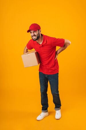 Full length portrait of upset delivery man in red uniform touching his painful back while holding packaging box isolated over yellow background Standard-Bild - 129805994
