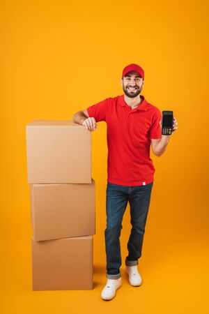 Portrait of unshaven delivery man in red uniform holding payment terminal while standing with packaging boxes isolated over yellow background Standard-Bild - 129805996
