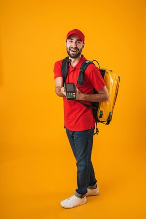 Photo of cheerful delivery man in red uniform holding payment terminal while carrying backpack with takeaway food isolated over yellow background Standard-Bild - 129805998