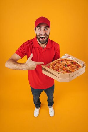 Full length image of attractive delivery man in red uniform smiling and holding pizza box isolated over yellow background Standard-Bild - 129806002