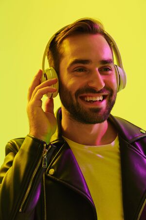 Close up of an attractive young man wearing leather jacket standing isolated over yellow background, listening to music with wireless headphones