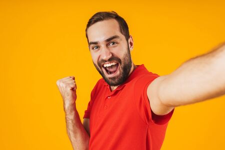Portrait of joyful man in red t-shirt laughing and rejoicing while taking selfie photo isolated over yellow background