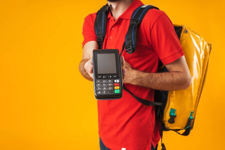 Cropped image of caucasian delivery man in red uniform holding payment terminal while carrying backpack with takeaway food isolated over yellow background Standard-Bild - 129806020