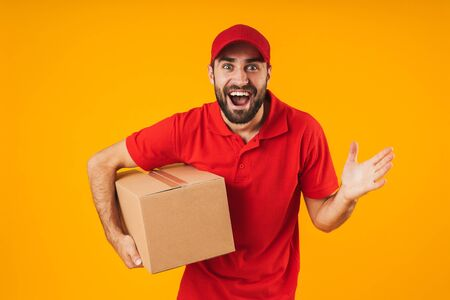 Portrait of excited delivery man in red uniform smiling and holding packaging box isolated over yellow background Standard-Bild - 129806023