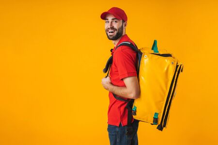 Photo of joyful delivery man in red uniform carrying backpack with takeaway food isolated over yellow background Standard-Bild - 129806024