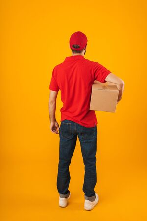 Full length portrait from back of young delivery man in red uniform holding packaging box isolated over yellow background Standard-Bild - 129806025