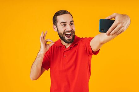 Portrait of positive man in red t-shirt laughing and showing ok sign while taking selfie photo on cellphone isolated over yellow background