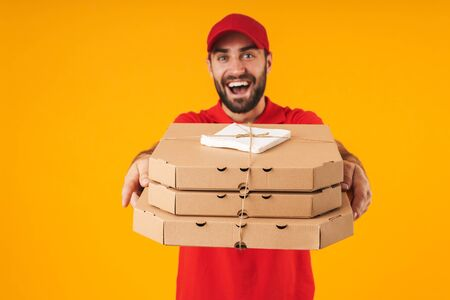 Portrait of handsome delivery man in red uniform smiling and holding pizza boxes isolated over yellow background Standard-Bild - 129806032