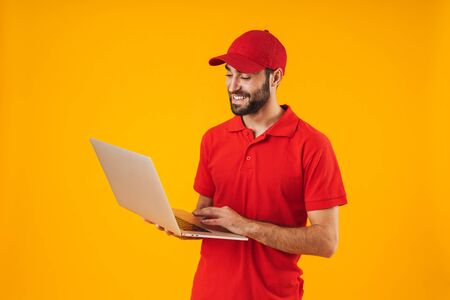 Portrait of young delivery man in red t-shirt and cap smiling and holding silver laptop computer isolated over yellow background Standard-Bild - 129806035