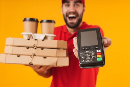 Portrait of handsome delivery man in red uniform holding pizza boxes and payment terminal isolated over yellow background