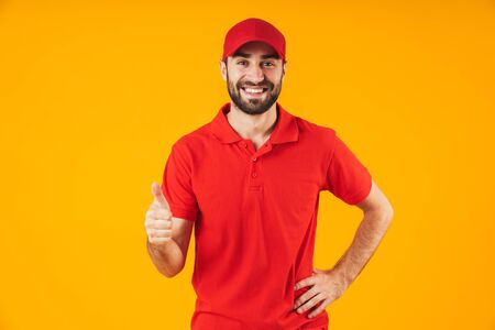 Portrait of attractive delivery man in red t-shirt and cap smiling and showing thumb up isolated over yellow background