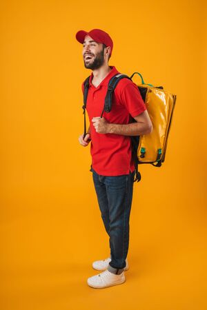 Image of smiling delivery man in red uniform carrying backpack with takeaway food isolated over yellow background Standard-Bild - 129806081