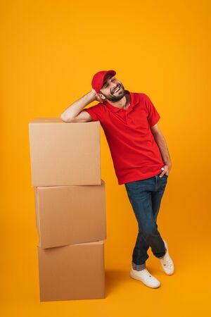 Portrait of happy delivery man in red uniform smiling while standing with packaging boxes isolated over yellow background Standard-Bild - 129806086