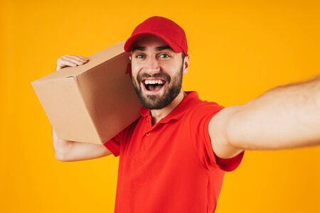 Portrait of handsome delivery man in red uniform smiling and holding parcel box while taking selfie photo isolated over yellow background Standard-Bild - 129806090
