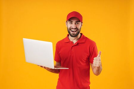 Portrait of positive delivery man in red t-shirt and cap smiling and holding silver laptop computer isolated over yellow background Standard-Bild - 129806094