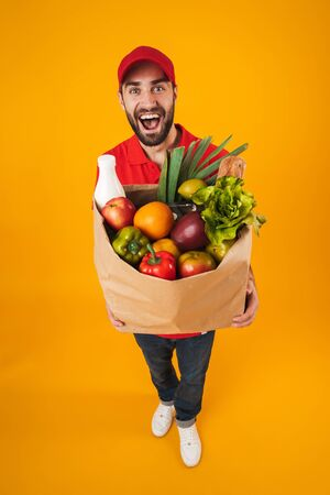 Portrait of excited delivery man in red uniform smiling while carrying paper bag with food products isolated over yellow background