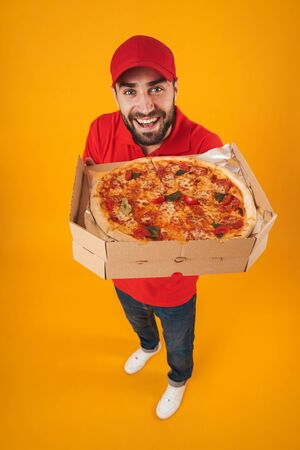 Full length image of handsome delivery man in red uniform smiling and holding pizza box isolated over yellow background Standard-Bild - 129806143