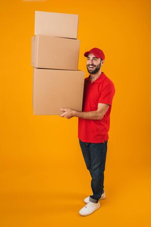 Full length portrait of pleased delivery man in red uniform smiling while carrying packaging boxes isolated over yellow background Standard-Bild - 129806144