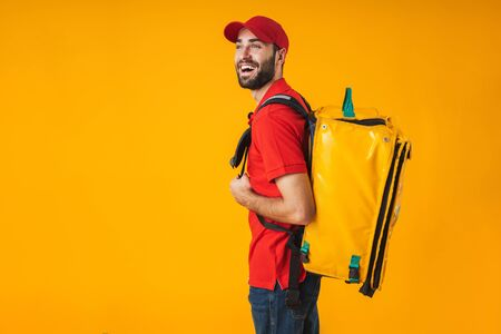 Photo of young delivery man in red uniform carrying backpack with takeaway food isolated over yellow background Standard-Bild - 129806146