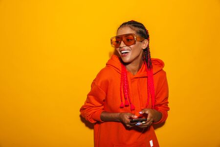Image closeup of positive african american woman wearing sunglasses and hoodie smiling while holding cellphone isolated over yellow background