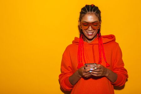 Image closeup of gorgeous african american woman wearing sunglasses and hoodie smiling while holding cellphone isolated over yellow background