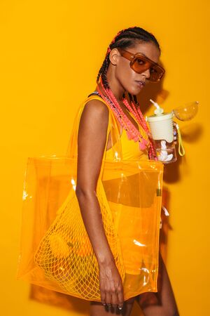 Image of alluring african american woman wearing sunglasses carrying bag and holding plastic cup isolated over yellow background