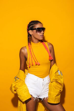 Image of fashionable african american woman wearing sunglasses and windcoat posing at camera isolated over yellow background
