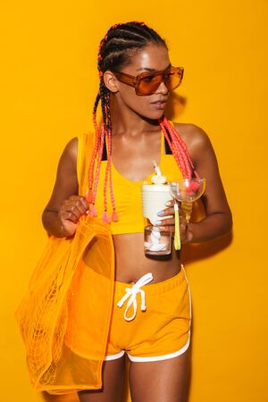 Image of lovely african american woman wearing sunglasses carrying bag and holding plastic cup isolated over yellow background