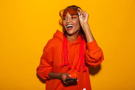 Image closeup of joyful african american woman wearing sunglasses and hoodie smiling while holding cellphone isolated over yellow background