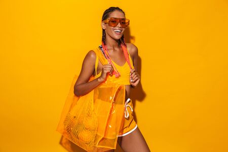 Image of cute african american woman wearing sunglasses carrying plastic bag and smiling isolated over yellow background