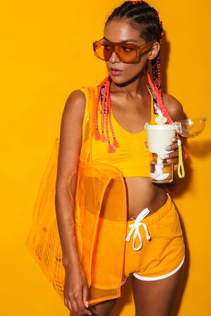 Image of seductive african american woman wearing sunglasses carrying bag and holding plastic cup isolated over yellow background