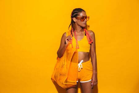 Image of attractive african american woman wearing sunglasses standing and carrying plastic bag isolated over yellow background