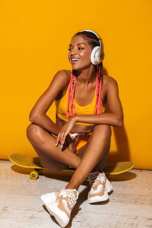 Image of pretty african american woman listening to music with headphones while sitting on skateboard isolated over yellow background