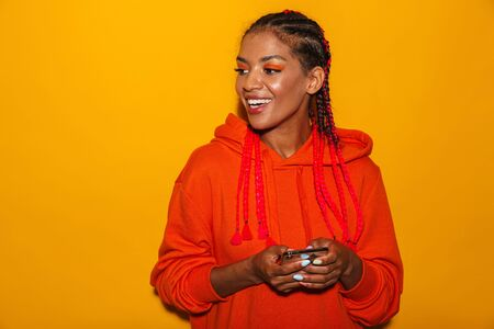 Image closeup of attractive african american woman wearing hoodie shirt smiling while holding cellphone isolated over yellow background