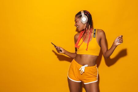 Image of positive african american woman singing while listening to music with smartphone and headphones isolated over yellow background