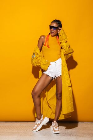 Image of pretty african american woman wearing sunglasses and windcoat posing at camera isolated over yellow background