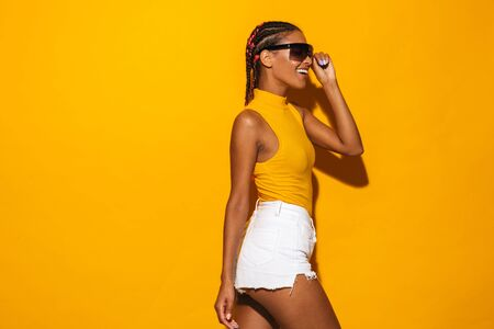 Image of joyful african american woman with afro braids wearing sunglasses looking aside at copyspace isolated over yellow background