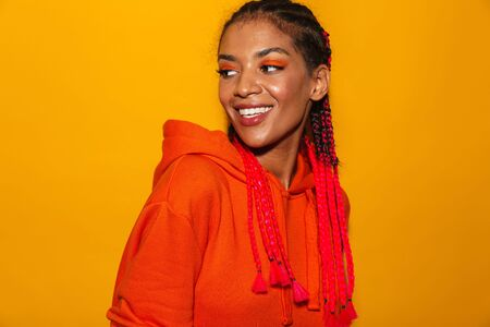 Image closeup of optimistic african american woman wearing red hoodie shirt smiling at camera isolated over yellow background