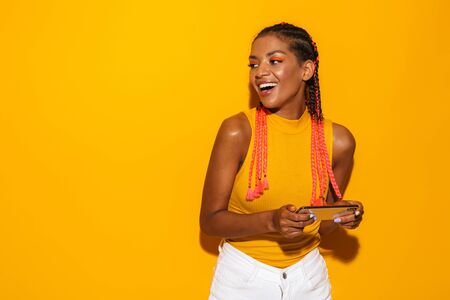 Image of cheerful african american woman with afro braids looking aside at copyspace and holding smartphone isolated over yellow background