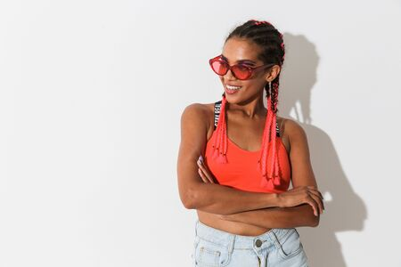 Photo of smiling happy young african woman posing isolated over white wall background wearing sunglasses.