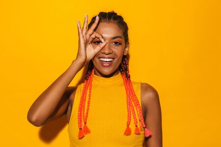 Image of gorgeous african american woman with afro braids smiling and showing ok sign at camera isolated over yellow background 写真素材