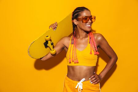 Image of nice african american woman wearing sunglasses holding skateboard and smiling isolated over yellow background