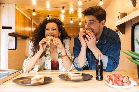 Happy young couple having lunch inside a trailer