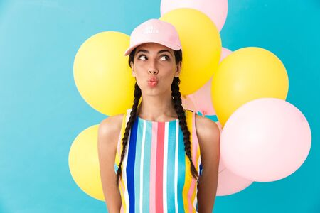 Image of cute seductive woman wearing cap making kiss lips while holding air balloons isolated over blue wall Фото со стока