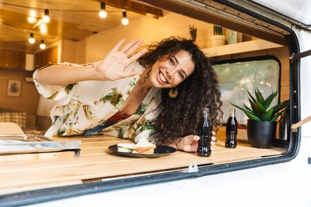 Beautiful young brunette woman standing inside a trailer, having lunch, waving hand Stock Photo